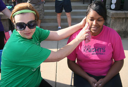 Martha Ann Mattingly applies a temporary Girls on the Run tattoo to Kim Bell's cheek before they start their turns on the treadmills.