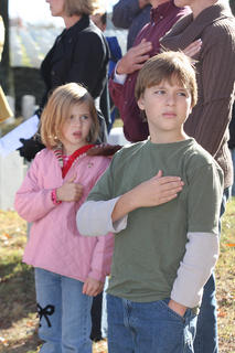Sam and Karis Smith hold their hands to their hearts as the Marion County High School JROTC post the colors at the Veteran's Day program at the Lebanon National Cemetery.