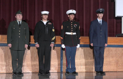 From left, James Bowles, Alex Hyatt, Jason York and Zach Jones stand at attention in the uniforms of the Army, Navy, Marines and Air Force respectively. A fifth cadet posted the flag and dressed in the uniform of the Coast Guard.