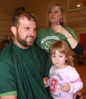 Brandon Lee sits down for his haircut and his daughter, Savannah, 3, sat on his lap.