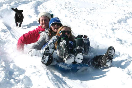 Jessie Miles, Savannah Chapman and Graci Wilson go sledding while Lucky the dog runs behind.