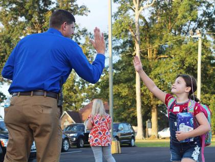 Fifth-grader Laken Thompson gets a high five from WMES Principal Daniel Mattingly before entering the building.
