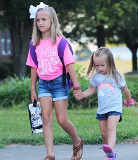 Second-grader Gracie Mattingly is accompanied by her younger sister to school.