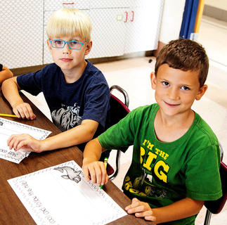 Lars Monaghan and Matthew Masterson write and spell rules during West Marion Elementary School's Little Pages Jumpstart.