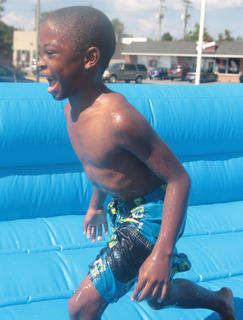 Tyval Furmon, 8, runs back to the line for another trip down the water slide.