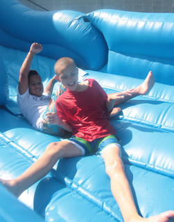 Kolby Scott, 10 (in the red shirt) and Jamison Epps, 9, get tangled up on their way down the water slide.
